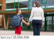 Купить «elementary student boy with mother at school yard», фото № 25056590, снято 24 июля 2016 г. (c) Syda Productions / Фотобанк Лори