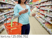 Купить «woman with smartphone buying milk at supermarket», фото № 25056702, снято 2 ноября 2016 г. (c) Syda Productions / Фотобанк Лори