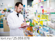 Купить «Pharmacist writing down assortment of drugs», фото № 25059078, снято 14 декабря 2016 г. (c) Яков Филимонов / Фотобанк Лори