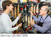 Купить «Ordinary customer and seller choosing hammer», фото № 25067554, снято 18 ноября 2018 г. (c) Яков Филимонов / Фотобанк Лори