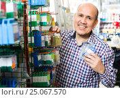 Купить «man choosing nails and screws», фото № 25067570, снято 18 ноября 2018 г. (c) Яков Филимонов / Фотобанк Лори