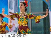 Девушки из фольклорно-танцевального ансамбля в национальной таджикской одежде выступает на сцене во время празднования Навруза в парке города Худжанд, Республика Таджикистан (2015 год). Редакционное фото, фотограф Николай Винокуров / Фотобанк Лори