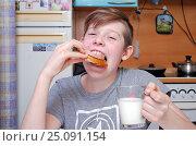 Купить «Подросток с удовольствием жует бутерброд с ветчиной и запивает молоком», фото № 25091154, снято 7 февраля 2017 г. (c) Глазков Владимир / Фотобанк Лори