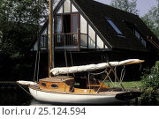 Купить «Small traditional cruising boat moored outside a chalet style house in the Norfolk Broads, UK 1995.», фото № 25124594, снято 24 января 2018 г. (c) Nature Picture Library / Фотобанк Лори