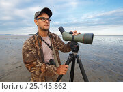 Купить «Birder looking for shorebirds on mudflats,  South Korea. October 2013.», фото № 25145862, снято 23 июля 2018 г. (c) Nature Picture Library / Фотобанк Лори