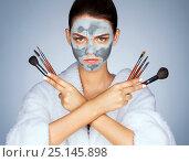 Купить «Serious woman holding up make-up brushes. Photo of young woman with mask of clay on her face. Beauty & Skin care concept», фото № 25145898, снято 7 сентября 2016 г. (c) Роман Егошин / Фотобанк Лори