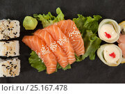 Купить «Uramaki and sashimi sushi served with chopsticks in black stone slate», фото № 25167478, снято 8 декабря 2016 г. (c) Wavebreak Media / Фотобанк Лори