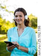 Купить «Woman listening music in mobile phone at park», фото № 25192198, снято 10 ноября 2016 г. (c) Wavebreak Media / Фотобанк Лори