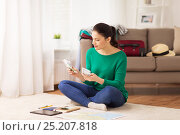 happy woman with money and travel map at home. Стоковое фото, фотограф Syda Productions / Фотобанк Лори