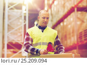 Купить «man in safety vest packing box at warehouse», фото № 25209094, снято 9 декабря 2015 г. (c) Syda Productions / Фотобанк Лори