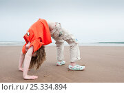 Купить «Young girl in 'crab' posture on a beach, Scotland, June 2009 Model released», фото № 25334894, снято 27 мая 2020 г. (c) Nature Picture Library / Фотобанк Лори