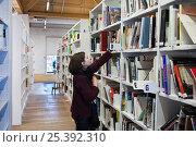 Купить «Девушка в библиотеке выбирает книгу», фото № 25392310, снято 11 февраля 2017 г. (c) Victoria Demidova / Фотобанк Лори