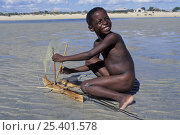 Vezo child playing on the beach with model pirogue, West Madagascar. Стоковое фото, фотограф Jouan Rius / Nature Picture Library / Фотобанк Лори