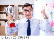 Купить «Young businessman receiving prize cup in office», фото № 25556878, снято 7 декабря 2016 г. (c) Elnur / Фотобанк Лори