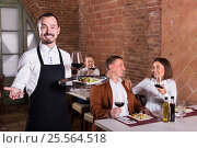 Купить «Young man waiter demonstrating country restaurant», фото № 25564518, снято 15 октября 2018 г. (c) Яков Филимонов / Фотобанк Лори