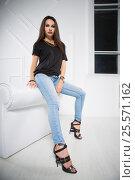 Купить «Young lady wearing blue jeans and black t-shirt», фото № 25571162, снято 30 августа 2015 г. (c) Сергей Сухоруков / Фотобанк Лори