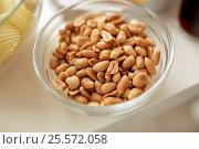 Купить «close up of roasted peanuts in glass bowl on table», фото № 25572058, снято 14 августа 2016 г. (c) Syda Productions / Фотобанк Лори
