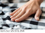 Купить «close up of hand with checkered clothing item», фото № 25572354, снято 15 сентября 2016 г. (c) Syda Productions / Фотобанк Лори