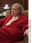 Elderly woman in red robe relaxing in a chair. Стоковое фото, фотограф Станислав Занегин / Фотобанк Лори