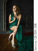 Купить «Elegant young woman in green evening dress posing in vintage interior», фото № 25591198, снято 8 сентября 2016 г. (c) Воронин Владимир Сергеевич / Фотобанк Лори