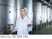 Купить «Positive young female in winery fermentation compartment», фото № 25594182, снято 15 сентября 2019 г. (c) Яков Филимонов / Фотобанк Лори