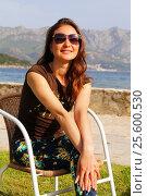 Купить «Счастливая девушка сидит в плетеном кресле на набережной на фоне гор», эксклюзивное фото № 25600530, снято 13 апреля 2016 г. (c) Артём Крылов / Фотобанк Лори
