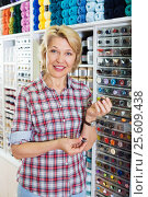 Купить «Mature glad woman customer picking various buttons», фото № 25609438, снято 14 июля 2020 г. (c) Яков Филимонов / Фотобанк Лори