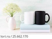 Купить «White and black mug mockup with books and white flowers», фото № 25662170, снято 30 июля 2016 г. (c) TasiPas / Фотобанк Лори
