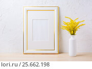 Купить «Gold decorated frame mockup with ornamental yellow flowering grass in vase», фото № 25662198, снято 19 августа 2016 г. (c) TasiPas / Фотобанк Лори
