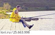 Купить «Family in yellow raincoats fishing», видеоролик № 25663998, снято 16 октября 2019 г. (c) Raev Denis / Фотобанк Лори