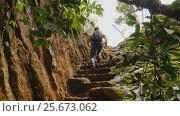 Купить «Tourist man climbing stairs into the rock. Beautiful nature. Vietnamese jungle near Elephant Falls.», видеоролик № 25673062, снято 3 марта 2017 г. (c) Mikhail Davidovich / Фотобанк Лори
