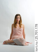 Fashion portrait of young beautiful blonde woman sitting on the floor, wearing elegant pink  top and long pink skirt, against white background. Стоковое фото, фотограф Мария Сидельникова / Фотобанк Лори