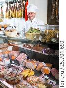 Купить «butcher with wurst at counter», фото № 25701690, снято 5 октября 2016 г. (c) Яков Филимонов / Фотобанк Лори