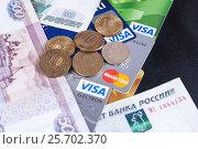 Купить «Пластиковые банковские карты, денежные купюры и металлические деньги лежать на черном фоне», фото № 25702370, снято 21 октября 2016 г. (c) Андрей Липинский / Фотобанк Лори