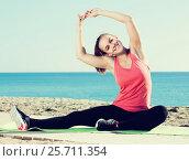 Купить «Happy young woman doing gymnastics exercises», фото № 25711354, снято 17 июля 2019 г. (c) Яков Филимонов / Фотобанк Лори