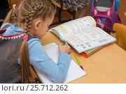 Купить «Первоклассница на уроке математики пишет в тетради, вид сбоку со спины», фото № 25712262, снято 28 февраля 2017 г. (c) Иванов Алексей / Фотобанк Лори