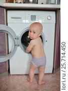 Купить «Little baby boy loading clothes into washing machine», фото № 25714450, снято 1 августа 2016 г. (c) Сергей Дорошенко / Фотобанк Лори