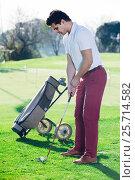 Купить «Man playing golf is going to hit ball at golf course», фото № 25714582, снято 14 ноября 2018 г. (c) Яков Филимонов / Фотобанк Лори