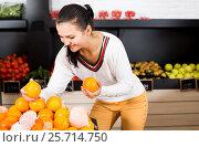 Купить «Female customer examining various fruits», фото № 25714750, снято 23 ноября 2016 г. (c) Яков Филимонов / Фотобанк Лори