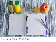 A notebook with a pencil, apple, juices and half a lemon on a wooden light table. Стоковое фото, фотограф Татьяна Дубчук / Фотобанк Лори