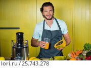 Купить «Portrait of smiling male staff holding glass of juice and papaya», фото № 25743278, снято 4 октября 2016 г. (c) Wavebreak Media / Фотобанк Лори