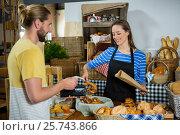 Купить «Smiling staff packing pretzel bread in paper bag at counter», фото № 25743866, снято 4 октября 2016 г. (c) Wavebreak Media / Фотобанк Лори