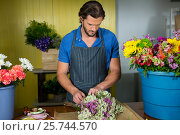 Купить «Male florist preparing a flower bouquet», фото № 25744570, снято 4 октября 2016 г. (c) Wavebreak Media / Фотобанк Лори