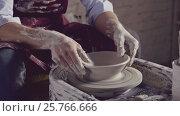 Купить «Young potter in uniform in workshop», видеоролик № 25766666, снято 25 сентября 2018 г. (c) Raev Denis / Фотобанк Лори