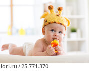 Купить «Funny baby boy in giraffe hat lying on his belly in nursery. Little kid using nibbler toy.», фото № 25771370, снято 3 марта 2017 г. (c) Оксана Кузьмина / Фотобанк Лори