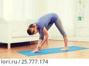 Купить «woman making yoga intense stretch pose on mat», фото № 25777174, снято 13 ноября 2015 г. (c) Syda Productions / Фотобанк Лори