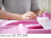 Купить «woman with pins stitching paper pattern to fabric», фото № 25777334, снято 29 сентября 2016 г. (c) Syda Productions / Фотобанк Лори