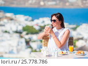 Girl having breakfast at outdoor cafe with amazing view. Woman enjoy her hot coffee early in the morning. Стоковое фото, фотограф Дмитрий Травников / Фотобанк Лори