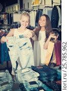 Купить «Smiling girls choosing denim trousers», фото № 25785962, снято 17 августа 2018 г. (c) Яков Филимонов / Фотобанк Лори