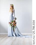 Купить «Spring beauty portrait of a bride with a wreath and a bouquet in hand», фото № 25786834, снято 11 апреля 2016 г. (c) Дарья Петренко / Фотобанк Лори
